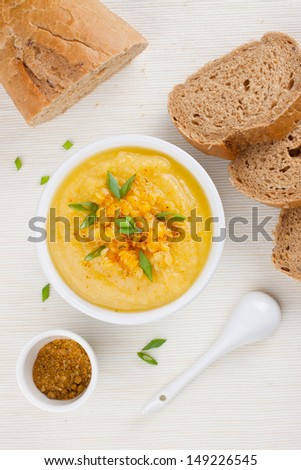 Yellow lentil soup in a bowl, garnished with bright green chives - stock photo