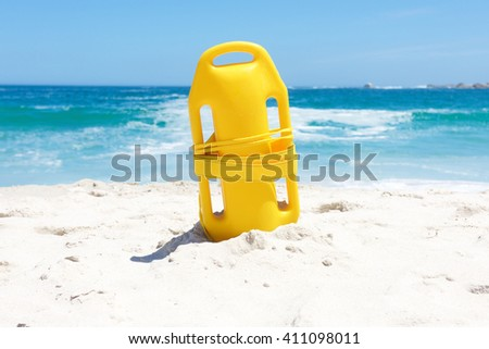 Yellow life saving buoy in sand at beach