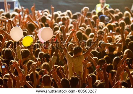 yellow lighted arded crowd at a live concert of a famous rockband - stock photo