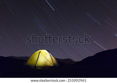 Yellow lighten tent under night sky - stock photo