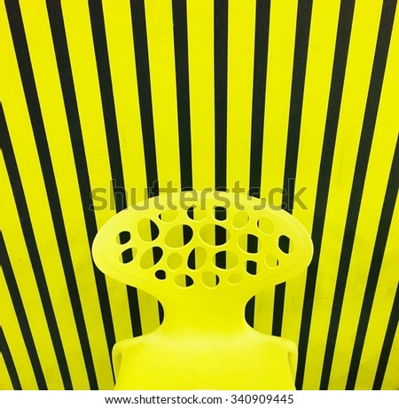 Yellow line and black line background with yellow chair and copy space on the wall - stock photo