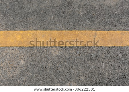 Yellow line dirty on black asphalt road texture - stock photo