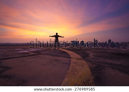 Yellow line lead to a happy man standing on the concrete floor of a skyscraper rooftop building watch a city sunset  - stock photo