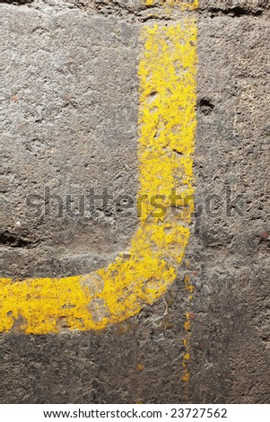 Yellow line on an old concrete floor makes a curve