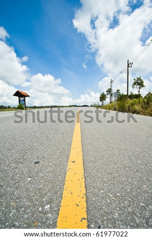 yellow line on road and blue sky - stock photo