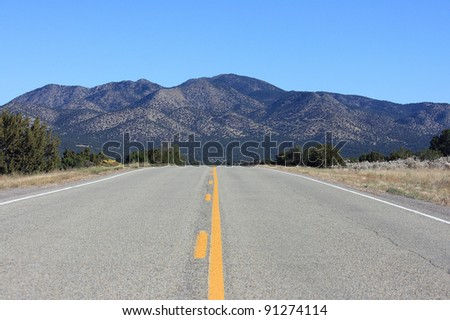 Yellow line road leading to mountains - stock photo
