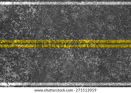 Yellow lines is painted on the asphalt road. - stock photo