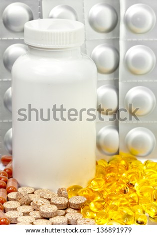 Yellow liquid capsules and silvery plates of medicines near a bottle