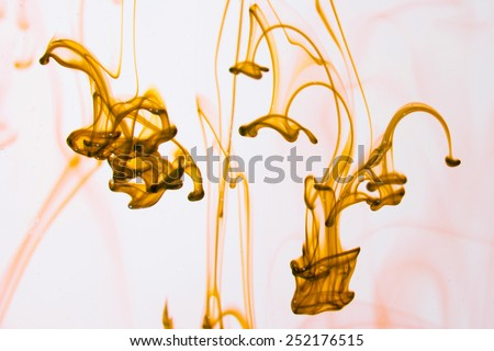 Yellow liquid in water making abstract forms - stock photo