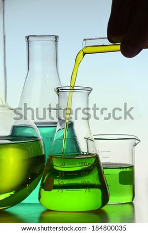 Yellow liquid pouring from test tube into a glass flask - stock photo