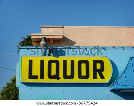 yellow liquor store sign on side of blue building - stock photo
