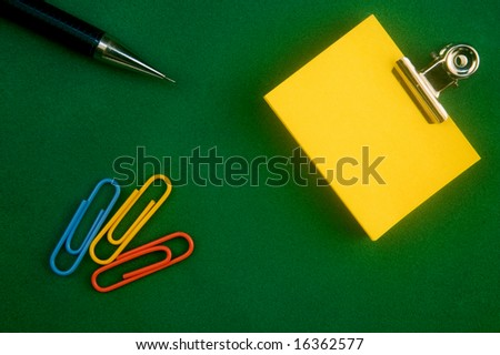 Yellow little Note Paper With Paperclip On green Surface - stock photo