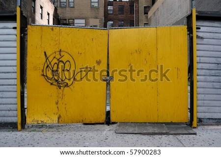 Yellow locked doors at an empty lot. - stock photo