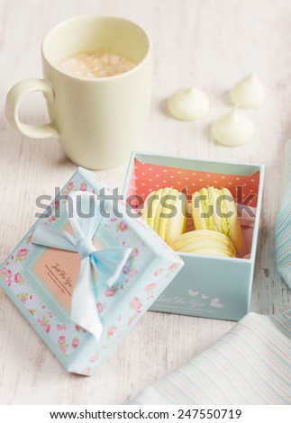 Yellow macaroons in gift box with cup of coffee. Pastel colored. Top view - stock photo
