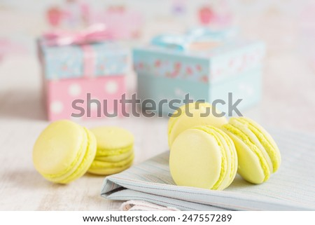 Yellow macaroons with gift boxes on background. Pastel colored  - stock photo