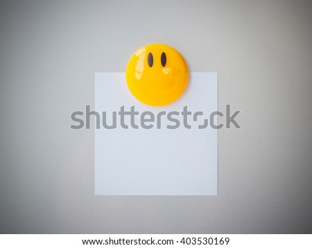 Yellow magnet paper clip on gray refrigerator background for input text, abstract background. - stock photo