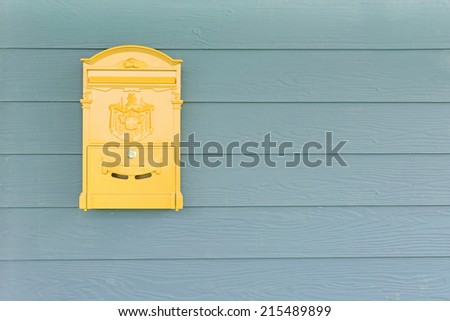 Yellow mailbox with green wood background - stock photo