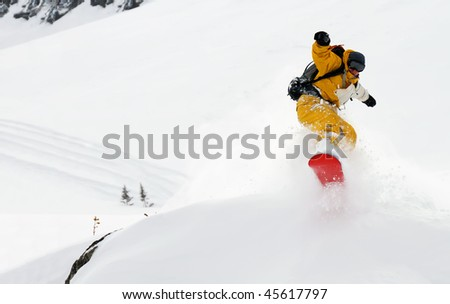 Yellow man snowboarder riding freeride and jumping high, splashing snow - stock photo