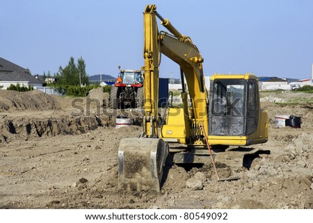 Yellow mechanical digger and tractor at a big job site after a day of removing dirt to install sewage and water line for a new neighborhood in rural North America. - stock photo