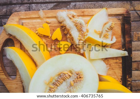 yellow melon Cantaloupe  slices with shape heart on broun background desk rustic style