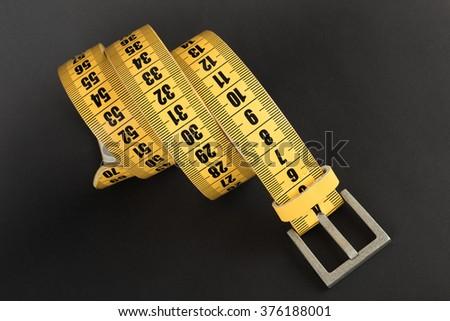 Yellow meter belt slimming on a black - stock photo