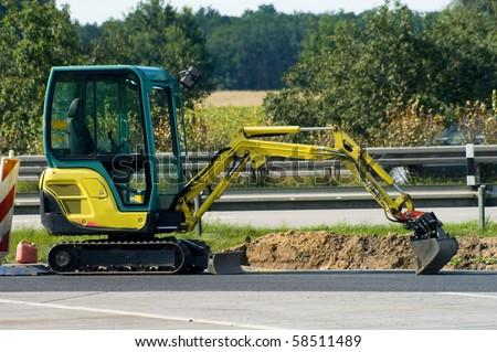 yellow mini excavator on  motorway - stock photo