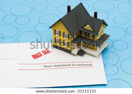Yellow model house with past due bills sitting on a blue background, foreclosure - stock photo