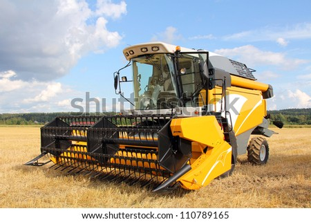 Yellow modern combine harvester on stubble field at end of summer. - stock photo