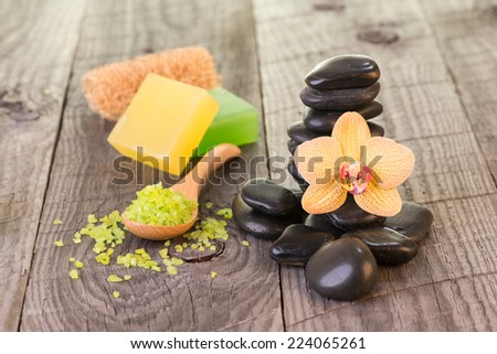 Yellow Moth orchid, black stones and soaps on weathered deck close up - stock photo