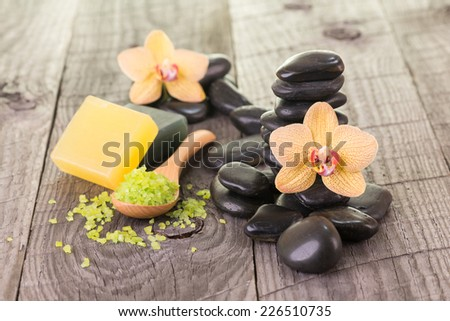 Yellow Moth orchids, soaps and black stones on weathered deck close up - stock photo