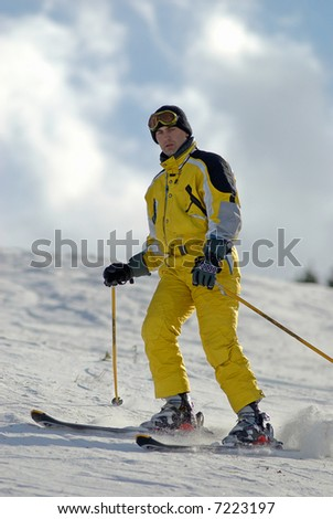 Yellow mountain skier on ski resort slope