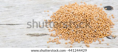 Yellow mustard seed over wooden background