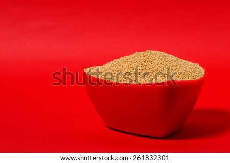 yellow mustard seeds in red bowl isolated on red background  - stock photo