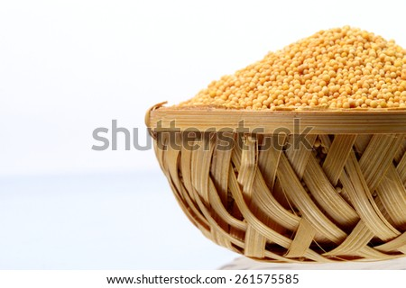 yellow mustard seeds in wooden basket isolated on white background  - stock photo