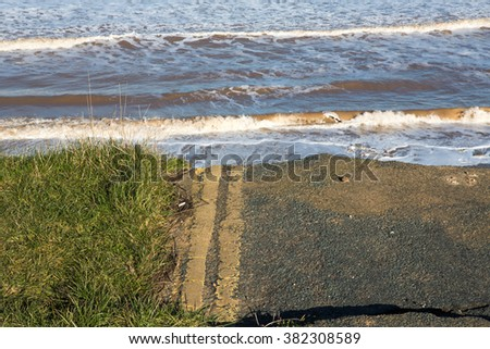 Yellow No Parking Lines on an old road that has has been washed away due to coastal erosion of the cliffs.  - stock photo