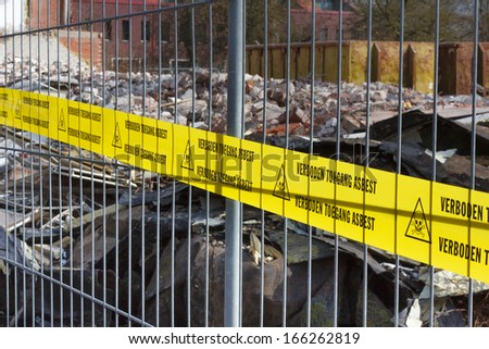 Yellow no Trespassing tape for asbestos in dutch at entrance of contaminated terrain - stock photo