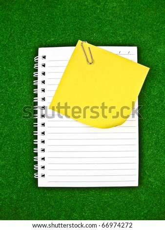Yellow note and Notebook Paper on green background - stock photo