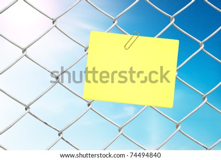 yellow note on chain link fence see blue sky - stock photo