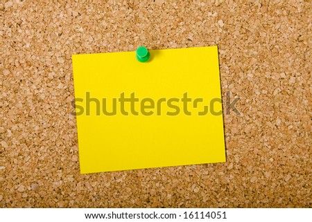 Yellow note paper pinned on a cork board