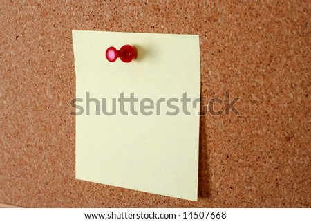 yellow note paper with tack on cork