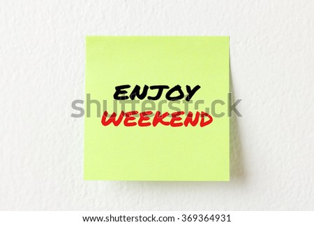 Yellow note paper with words Enjoy weekend on the white wall