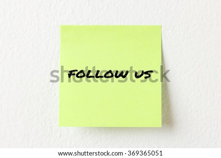 Yellow note paper with words Follow us on the white wall
