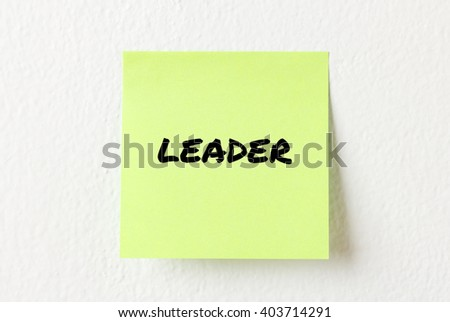 Yellow note paper with words Leader on the white wall
