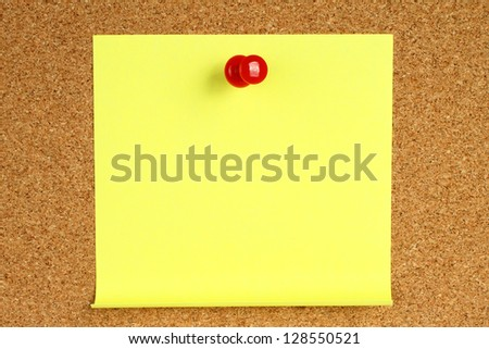 Yellow note with pin on wooden background