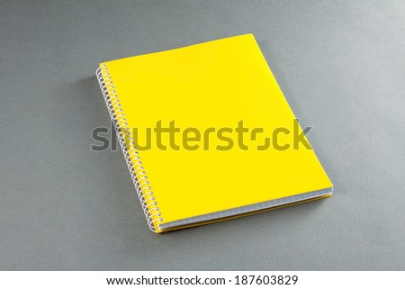 Yellow notebook on a gray background - stock photo