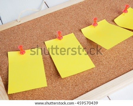 Yellow notes with pins on cork board.