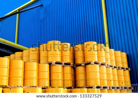 Yellow oil drums in front of a factory with blue cladding - stock photo