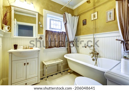 Yellow old bathroom interior with white plank paneled wall trim and antique vanity and bath tub - stock photo