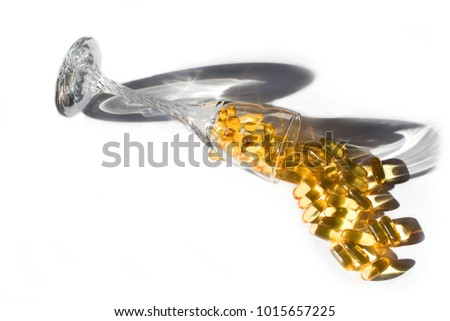 Yellow Omega 3 fish oil capsules in glass on white neutral background with shadows