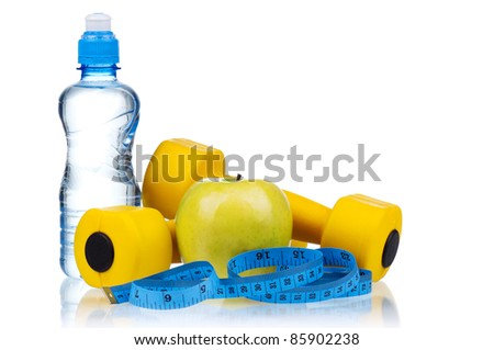 Yellow one kilogram dumbbells with apple, bottled water and measuring tape isolated on white background - stock photo